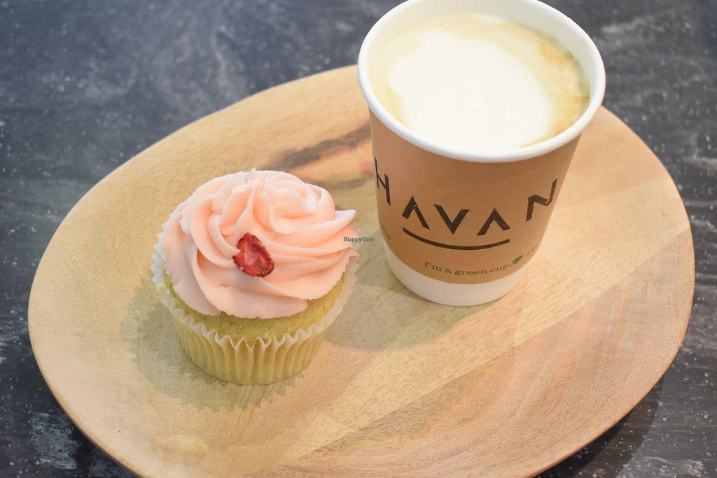 Coffee and a cupcake with pink frosting on a wooden board on a marble surface