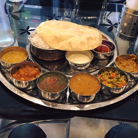 curries in metal bowls from crispy dosa with rice with a poppadom stacked on top