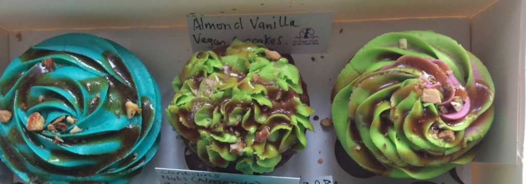 Photos from It's Vegan Made's Facebook page of brightly coloured blue and green-frosted cupcakes in a box