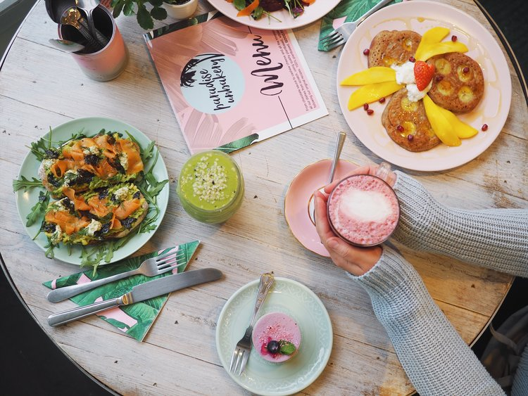 Picture from Paradise Plantbased of someone holding a brightly coloured pink smoothie with a table laid with food and a bright green smoothie