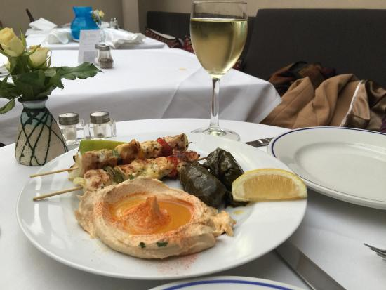 Picture of a meal from Jakobs on a white plate of lemon, hummus and kebabs