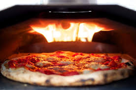 Picture of a pizza with bubbling cheese in a stone oven with burnt dough crust