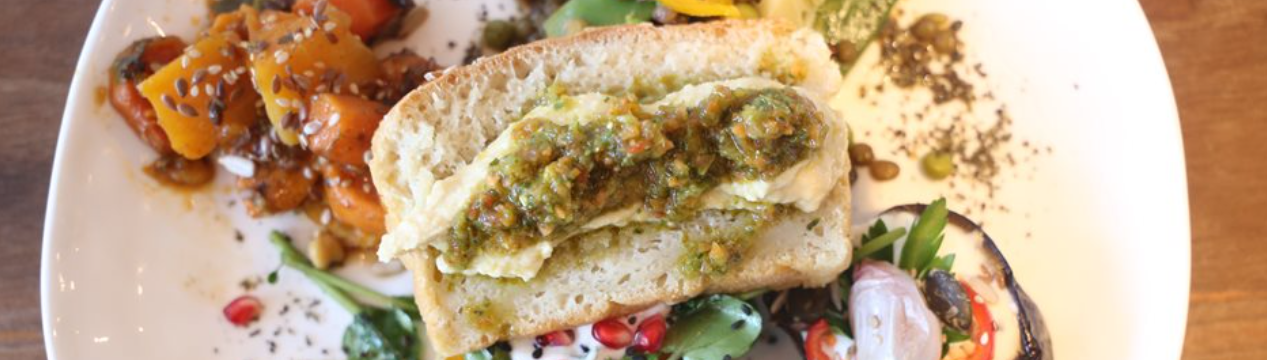 Picture of a vegan dish of vegetables on a plate topped with bread and salsa