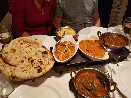 Picture of curries in white boats and a metal bowl with a large naan