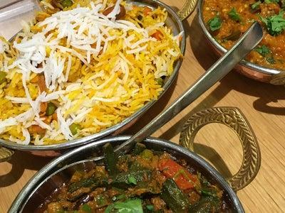 Picture of dishes of pilau rice and curry in a pot with curltery