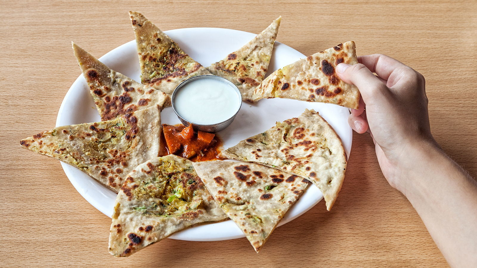 Picture of dosa or naan with dip on a plate on a table