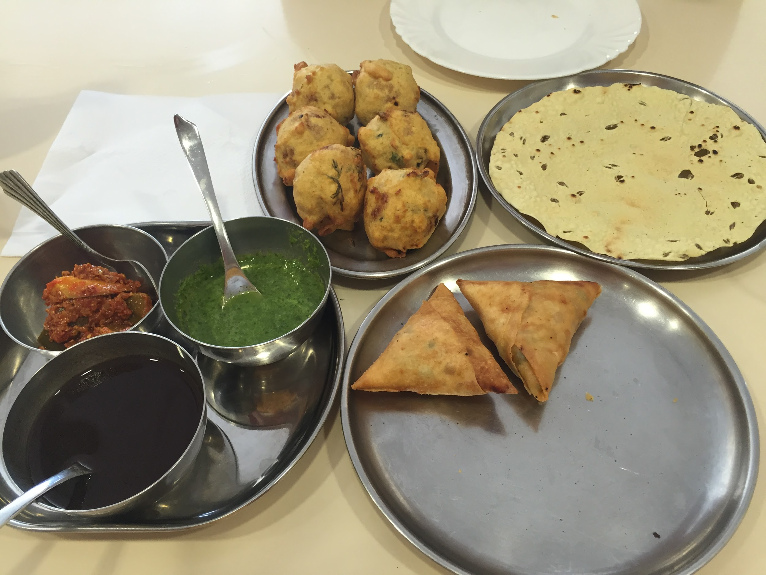 Pictures of curries and dips with spoons sticking out of them with naan on a table