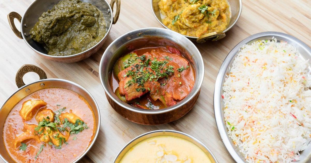 Pictures of curries and rice in dishes on a wooden table