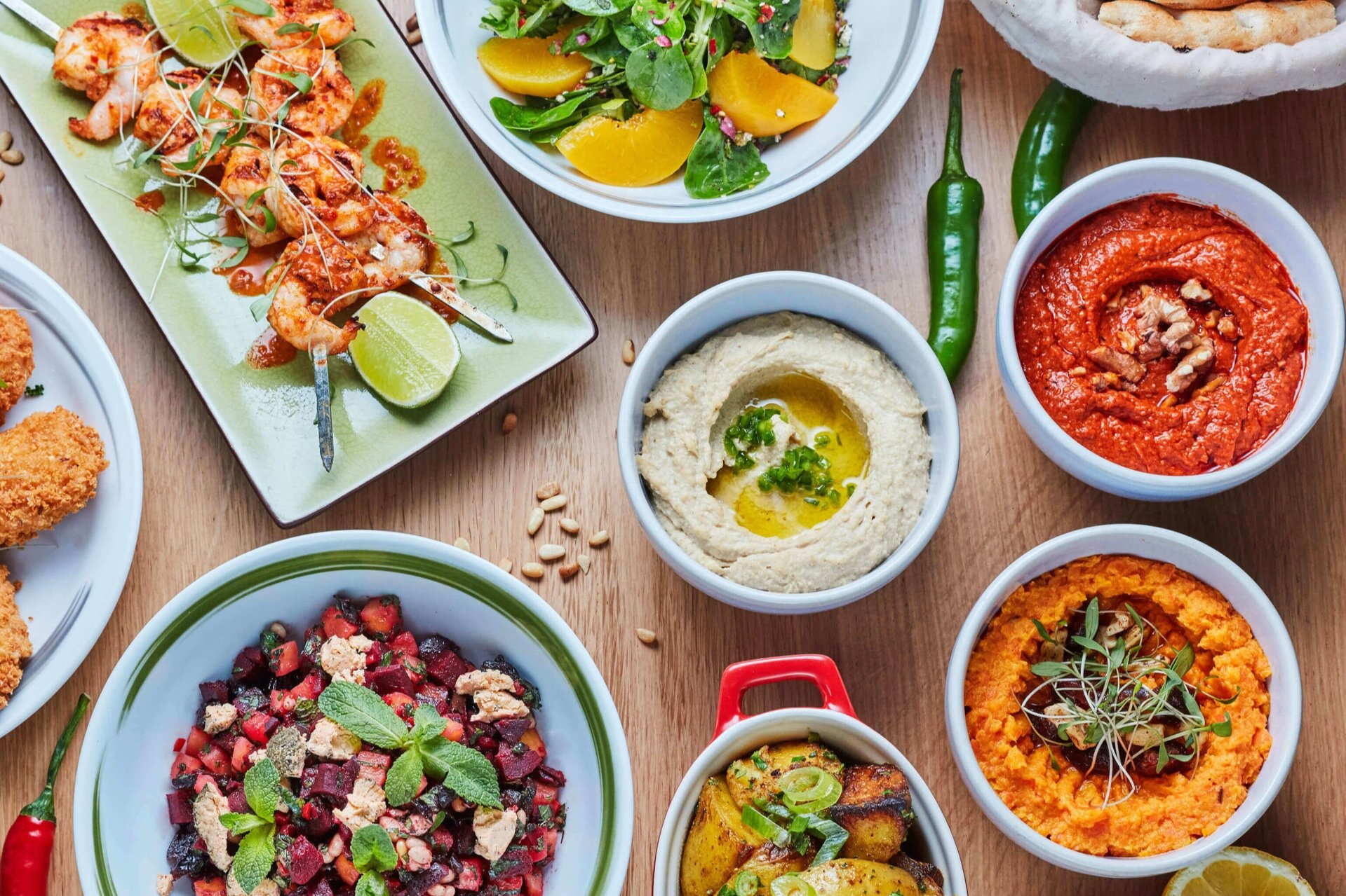 Table filled with bowls of food from Ceru like hummus and dips with chillies and nuts on a wooden table